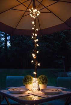 Dinner party perfection! Wrap string lights around a bistro table umbrella, create mason jar fairy lights and add a few potted plants or flower bud vases to complete the display.