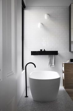 Modern Black and White Bathroom design with subway tiles from floor to ceiling, touches of black and a mix with wood.