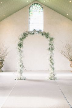 a simple chapel and baby's breath arch and decor | via coco kelley