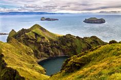 View from top of Heimaklettur in Vestmannaeyjar, Iceland.The island to left is Elliðaey, and on right is Bjarnarey.Eyjafjallajökull is hidden in the clouds.