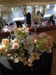 Centerpiece set of glass cubes filled with white hydrangea, mini green hydrangea, Dusty Miller, peach stock, peach roses and seeded eucalyptus surrounded by diamond banded pedestal stands with floating candles