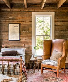 The guest bedroom in this rustic log cabin seamlessly merges the old (a map of Vashon Island from the 1920s) with the new (a supple leather armchair from retailer J. Peterman).