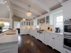 Contemporary Kitchen with full backsplash, Flat panel cabinets, Simple marble counters, can lights, Columns, Casement