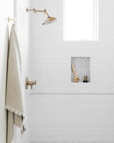 White and gray marble herringbone floor tiles in a shower fitted with white beveled subway tiles and a brushed gold shower kit. White Beveled Subway Tile, White Subway Tile Bathroom, Subway Tile Showers, Small Bathroom, Bathroom Bin, Glass Bathroom, Bathroom Ideas, Bathroom Designs, Bathroom Showers