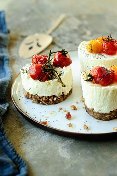 Creamy cheesecakes with goat cheese on a crispy crackers crust, served with roasted cherry tomatoes and poppy seeds. The crust is slightly sweetened with