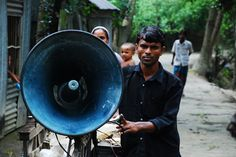 A villager in rural Bangladesh tests a community-driven early warning system. Credit: UNISDR