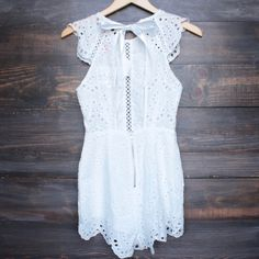 Gorgeous sleeveless round neck white romper that features an open back and crochet eyelet detailing throughout. lined but may appear semi-sheer open back impor