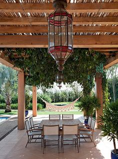 """Graças à proteção do extenso pergolado de cumaru, este canto pode incluir mesa para refeições ao ar livre e até rede. """"O segredo da sombra f..."""