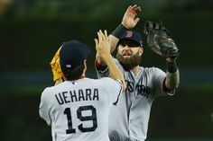 Mike Napoli #12 and Koji Uehara #19 of the Boston Red Sox celebrate their 1 to 0 win over the Detroit Tigers during Game Three of the ALCS.
