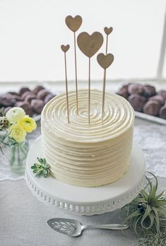 A simple one-tier white wedding cake with heart toppers | Brides.com