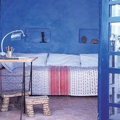 chambre aux murs bleus, dessus de lit blanc avec imprimé rouge, niches dans le mur
