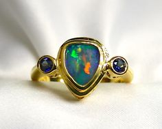 Ladies Gondwanaland Design Solid Opal 18K Yellow Gold Ring with Blue Sapphire Accents is an awesome new creation. The trillion shape solid Opal
