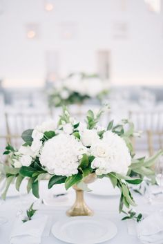 Instead of a mix of varying blooms, one type of flower really makes a statement in a centerpiece, especially when it's stark white popping against deep green in a tall gold bowl.
