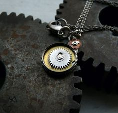 Que is made from recycled watch parts, including a brass spring barrel, a small gear, a tiny copper wheel, a watch plate, and a steel balance wheel. All parts have been soldered together using lead free silver bearing solder, never glued, in order to last. Wheel is designed and hand arranged by a human, and is not just a mass produced watch movement attached to a chain. There will never be another exactly the same, as we strive for orginality and creativity.