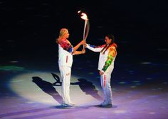 Olympic torch bearer Maria Sharapova passes on the Olympic torch to Elena Isinbeava during the Opening Ceremony of the Sochi 2014 Winter Oly...