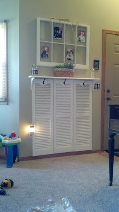 Repurposed shutters in lieu of wainscoting for an entryway organizer. Hooks for coats/backpacks & shelf above for keys/outgoing mail.
