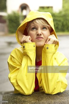 Woman in a yellow hooded raincoat looking grim up into the sky : Stock-Foto