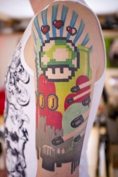 Awesome pixelated Mario tattoo with 1-up mushroom, coins, level pipes and bullets