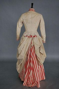 Description: An unusual printed cotton Independence day dress, circa 1876, of inexpensive striped and spotted calico trimmed with red and white lace, the un-boned bodice with stand collar, short tabs to the back, over draped and polonaised skirt, bust 86cm, 34in, waist 71cm, 28in (2)