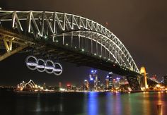 It is a display of four life-size Audi cars, suspended inside the silver rings of a massive Audi symbol attached to an iconic bridge structure or in front of landmark spaces — the Sydney Harbour Bridge, Brooklyn Bridge, Tower Bridge, Venice (SO) Bridge Structure, Arch Bridge, Tower Bridge, Places To Travel, Places To See, Famous Bridges, Best Ads, Guinness World, Middlesbrough