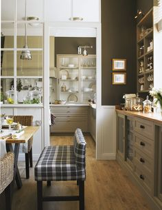 gorgeous kitchen - chocolate brown walls, gray cabinets, white trim, and a glass partition between the kitchen and dining room to separate the rooms but still let light in