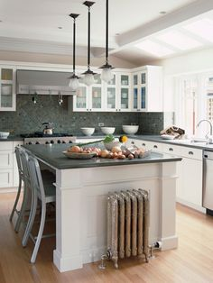A kitchen island doubles as an eating area with stainless-steel bar stools that can be tucked under the island when not in use -- #kitchens #decor #family