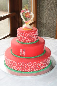 "Chinese Themed Wedding Cake. Vanilla cake with raspberry filling, iced with butter cream, covered with red marshmallow fondant then detailed with butter cream. Chinese symbol is ""double happiness""."