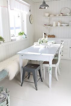 white wooden table, faux fur rug, wooden walls, speckles of plants.
