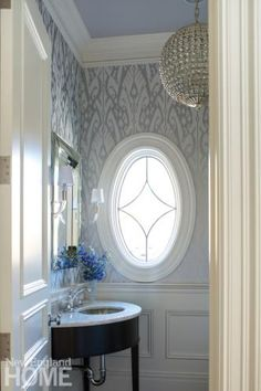 A giant ikat print wallcovering by Jerry Pair flows around the first-floor powder room's charming oval window. Architecture by E. Ronald Gushue, ERG Architect,; interior design by Michelle Morgan Harrison, Morgan Harrison Home,; photography by John Gould Bressler  Opposites Enhance | New England Home Magazine