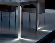 the luna table by Manutti features a simple look, free of adornment except for the slim, subtle strips of LED light running up and down its legs