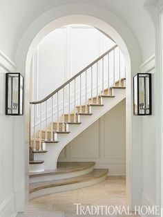 A stunning curved staircase can be glimpsed through the archway. - Traditional Home ®/ Photo: Emily Jenkins Followill / Architect: Ken Pursley and Craig Dixon