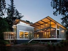 "Modern minimalist glass home contemporary design inspiration by RobertvM.Cain Architect, located in Decatur, Georgia. This modern house called RainShine house, has the living room, dining, kitchen and guest bedrooms are sheltered by a unique butterfly roof structured with steel beams spanned by exposed 1- 1/2"" tongue-and-groove wood decking."