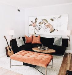 CONTRAST: the peach and coral colors of the throw pillows, painting, and ottoman burst agains the otherwise neutral living room with it's black couch and white paint. The orange ties well in with the wooden floor and makes the room feel grounded as it lightens on the way up towards the ceiling.