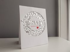 twinkly circle-ring shaker card filled with silver stars! Love the simple pop of red on the sentiment and the heart, leaving the rest of the card all white and silver. There are good directions so you can CAS this handmade Christmas card.