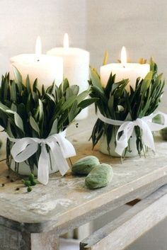 Chunky pillar candles tied with olive leaves and white ribbon to decorate a mantlepiece.