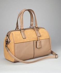 Trendsetting in two complementary hues, this faux leather satchel is classic yet cutting edge. A faux suede finish details the exterior, while the zippered interior boasts a single zip compartment. Opt for the detachable strap for hands-free traveling.13'' W x 10'' H x 7'' DShell: PVCLining: cotton