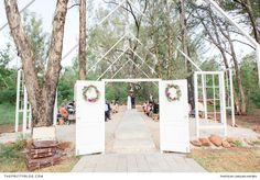 Create an eye-catching entrance for your ceremony venue by attaching a white wooden door to each side of an arch. | Photographer: Carolien and Ben
