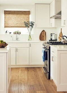 Classic kitchen with white cabinents, wood floors, and a white island