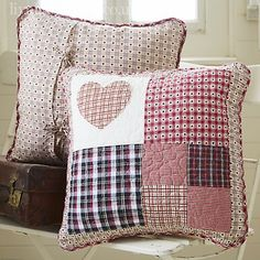 Pretty quilted patchwork cushion . A mixture of gingham and checks make up a patchwork heart in the centre. Reverse is raspberry gingham. 40cm square. 100% Cotton. Machine Washable.