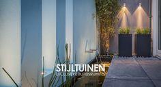 Tuin met lichtblauwe muur, waterloopjes en vijver, plantenbakken met siergrassen, sfeervolle tuinverlichting. www.stijltuinen.nl