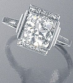 DIAMOND RING, BY MELLERIO DITS MELLER, CIRCA 1930. Centring a cushion-cut diamond weighing 2.54 carats, mounted in platinum and flanked by baguette-cut diamonds,