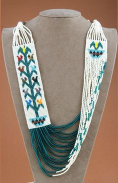"Beaded Necklace, Rena Charles: Here, Rena features the tree-of-life pictorial textile pattern, actually birds sitting on a sacred corn stalk, which ""grows"" out of a Navajo wedding basket. Rena is one of a few artists that have adapted the Navajo rug styles to these beaded necklaces."