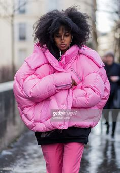 Julia Sarr Jamois wearing a huge pink feather down jacket and a black hoody, pink pants outside Rochas during the Paris Fashion Week Womenswear Fall/Winter 2016/2017 on March 2, 2016 in Paris, France.