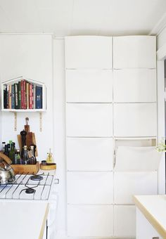 Kitchen storage - 12 Ikea 'Trones' shoe boxes on a whole wall is perfect for any storage you would like: dishtowels, cookbooks, napkins and shoes!