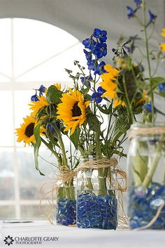 Table arrangements. Different flowers, but I love the main jars abd marbles!