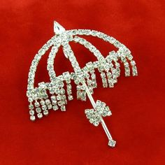 Not just another umbrella brooch! With a sparkling clear rhinestone bow tie, this umbrella brooch dazzles with rhinestone definition and....dangles! Rows of clear rhinestones recreate water drops cascading beneath this umbrella. They move and sway as a fringe of glitter. Unique and glamorous. Has a silver tone metal loop on the reverse so you can enjoy this umbrella pin as a pendant.