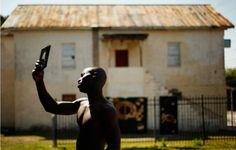 フロリダ・サンフォードの町で光の中、青年が父親に切ってもらった髪を鏡で確認している。