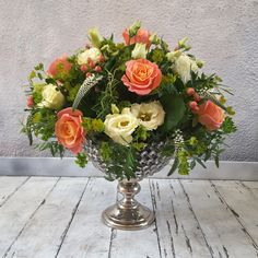 Floral table arrangement in #peaches, #creams and #whites with #green and #limegreen foliage. #Arrangement sits in a silver, #jewelled #container. #Flowers include #Roses, #Lisianthus, #Veronica, #Hypericum #berries and #Rosemary. Table Centers, Container Flowers, Table Arrangements, Surrey, Peaches, Corporate Events, Veronica, Berries, Floral Wreath