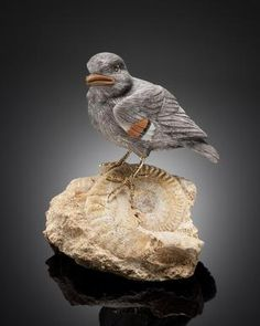 By Manfred Wild Idar-Oberstein, Germany   Carved of grey obsidian, the present carving of a finch is highlighted with a jasper beak and accents to the wings.  The gold vermeil feet rest upon the fossil base suggesting a landscape.   Height 4in