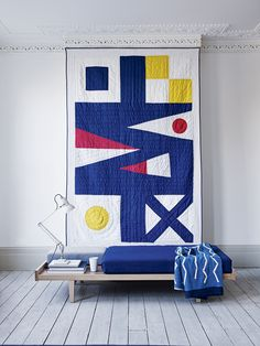 Summer updates: transform a quilt into a piece of art and display as a wall-hanging. We love the bold primary colours and graphic flag design of this one from Lexington teamed with Pierre Paulin for Ligne Roset's daybed   Photograph Jake Curtis, styling Emma Thomas   Homes & Gardens